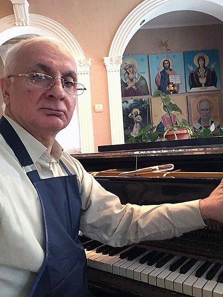 мастер музыкальных инструментов за работой с роялем Шредер